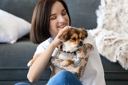 Beautiful tattooed woman with cute dog at home