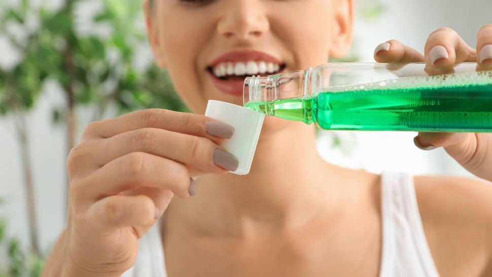 Woman pouring mouthwash from bottle into cap, closeup. Teeth care
