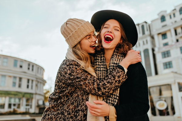 Carefree girl in brown hat embracing her sister. Outdoor photo of happy ladies spending autumn weekend together.