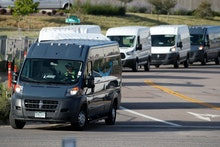 R m. Graph, vans queue up to leave an Amazon delivery center in suburban Englewood, Colo