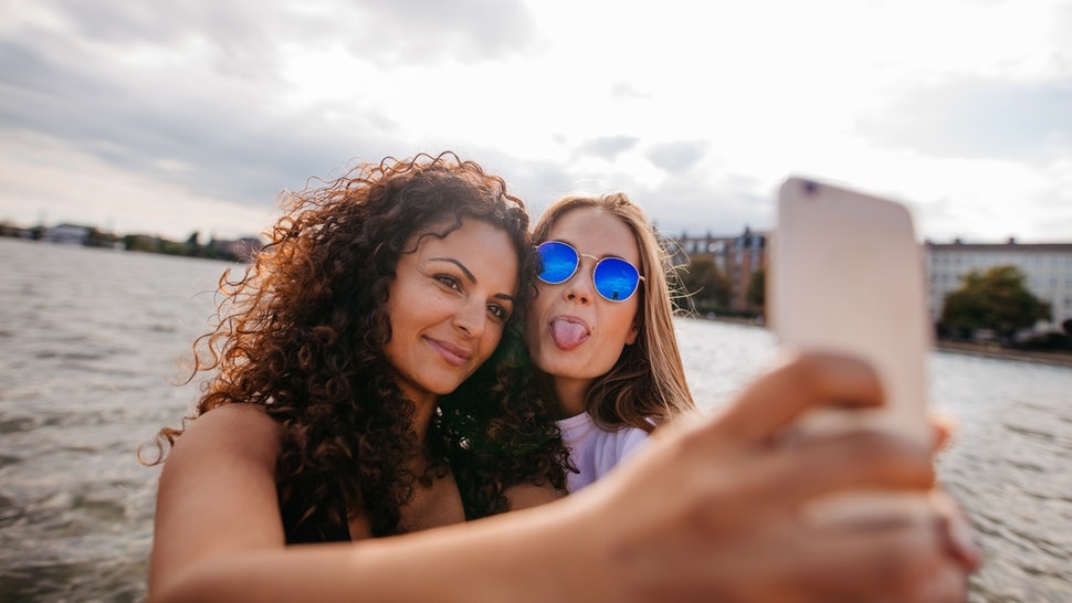 Shot of teenage girls taking selfie with smart phone by the lake. One sticking out tongue with other holding mobile phone.