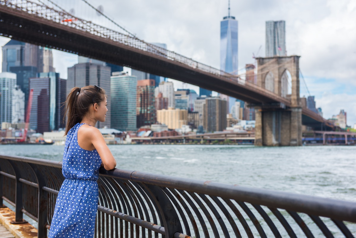 New York city urban woman enjoying view of Brooklyn bridge and NYC skyline living a happy lifestyle walking during summer travel in USA. Female Asian tourist in her 20s.