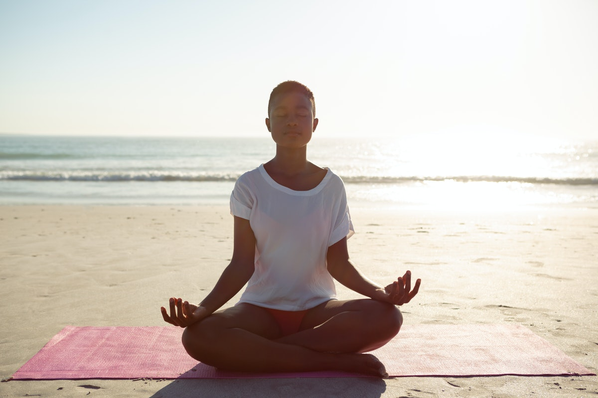 Front view of African-american woman performing yoga on the beach