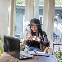 Charming beautiful tan skin Asian business chic woman hand work on laptop phone and write pen on notebook dairy on wooden table in coffee shop . Presenting your product with good looking woman face.