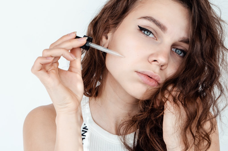young beautiful curly woman uses white serum for face. The concept of facial skin and hair care.