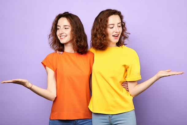 beautiful identical sisters twins holding copyspace on the palms isolated on a blue background, girls offer choise, scale, woman thinking about advantages and disadvantages of problem