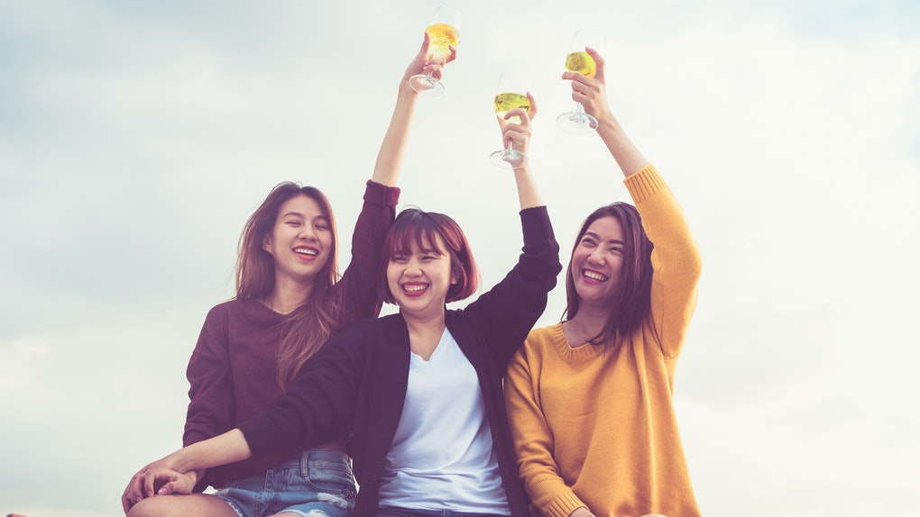 Three friends raise up their white wine glasses outside.