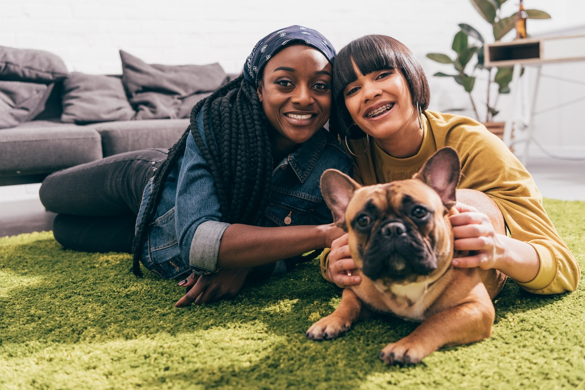 A woman and her dog are bonding with her partner while laying on a green rug.