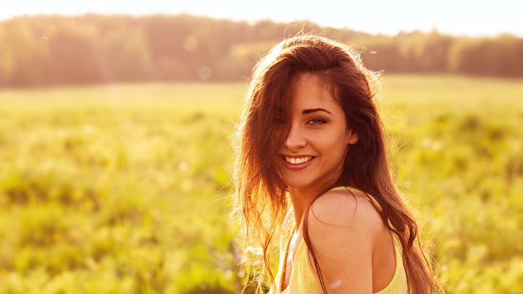 Beautiful toothy natural smiling relaxing woman looking happy with long amazing hair on nature bright sunset summer background. Closeup portrait