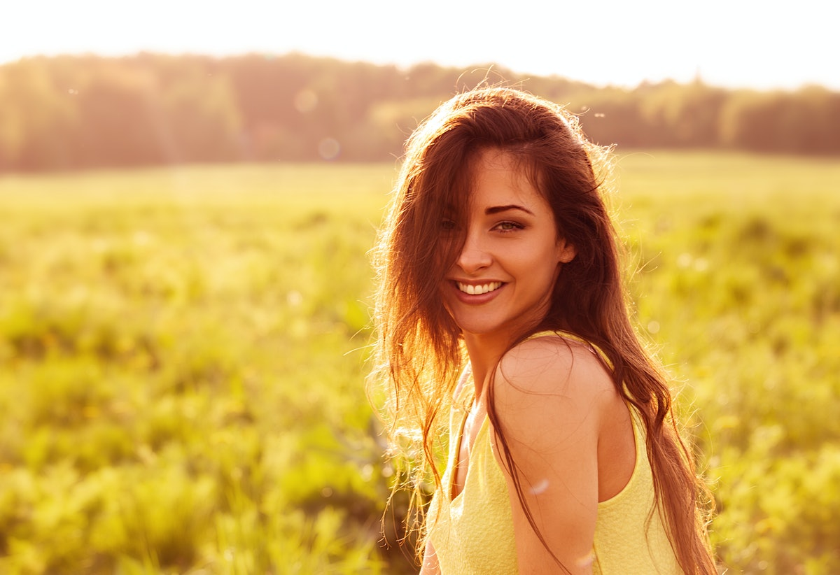 Beautiful toothy natural smiling relaxing woman looking happy with long amazing hair on nature brigh...