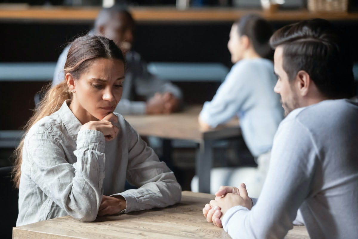 Shy or bored mixed race woman sitting at table in cafe during speed dating indifferent to the conver...