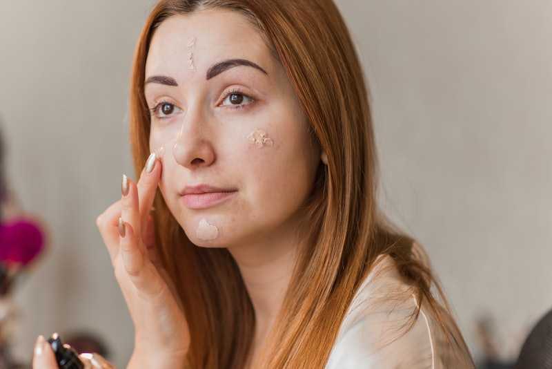 Woman applying foundation and concealer makeup. Do it yourself makeup for problem skin