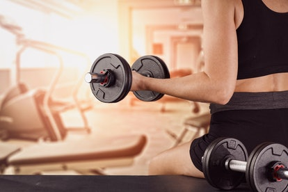 Dumbbell, barbell and workout in the gym. Woman lifting weights.