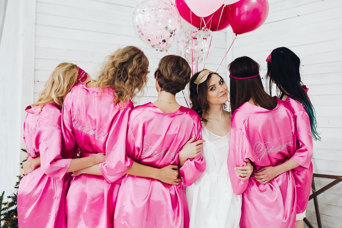 Back view of group of bridesmaids with bride-to-be in beautiful silk robes with different names on their backs.
