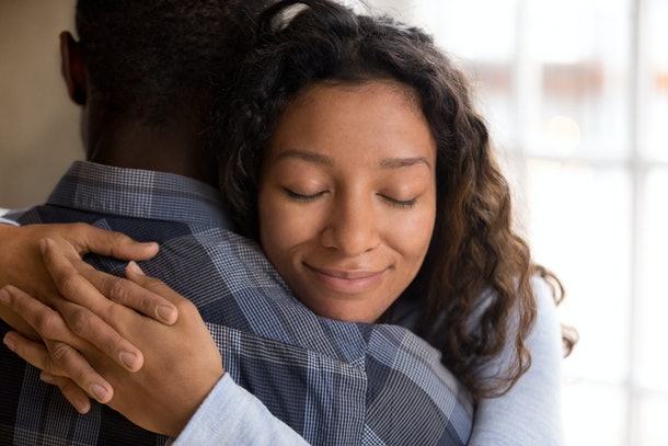 Happy african american wife hugging husband holding tight feeling grateful, smiling woman in love embracing beloved man, young black couple cuddling, support, sincere devotion and affection concept