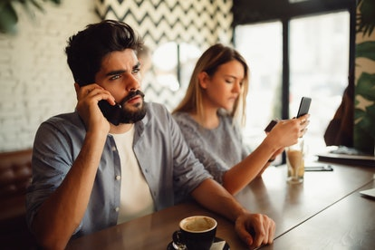 A beautiful young woman is upset to her handsome boyfriend because he is talking on the phone while they are having a coffee on the table.
