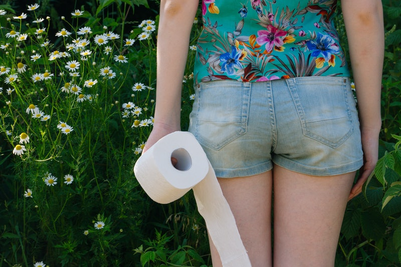 Woman take toilet paper. Back view. Concept of diarrhea. Natural toilet paper