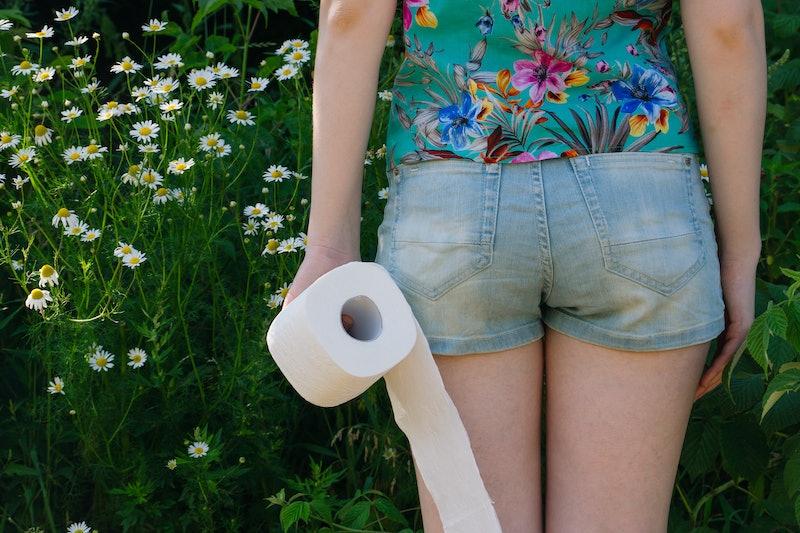 Woman take toilet paper. Back view. Concept of diarrhea. Natural toilet paper