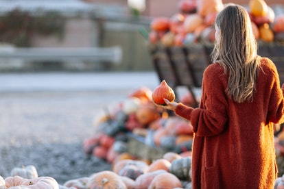 Back view of woman with small pumpkin in hand near wooden wagon with pumpkin on farmers market in br...