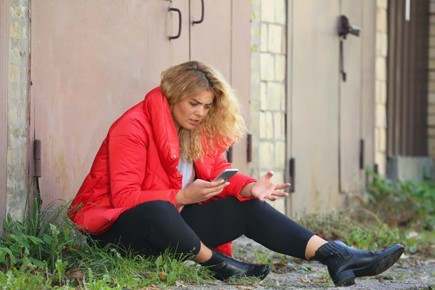 Depressed young woman with mobile phone sitting on ground outdoors