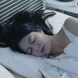 Portrait of sleeping woman having nightmares lying in comfort warm white bed cover by blanket. beautiful asian female frowning sleep in midnight at home. bad quality of restless young people.