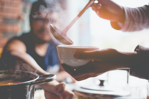 Woman holding ladle in the hand for preparing dinner.