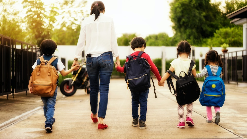 Mom and four kindergarten kids holding hand carry schoolbag walking to school bus.preschool concept.first day of semester