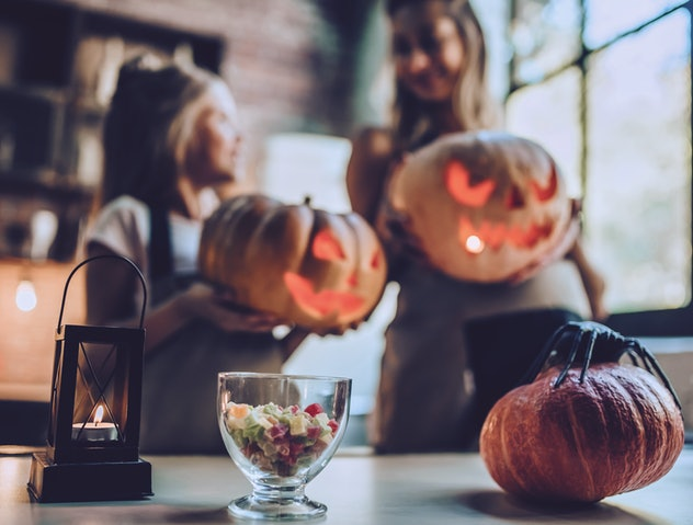 Happy Halloween! Attractive young pregnant woman with her little cute daughter are preparing to Hall...