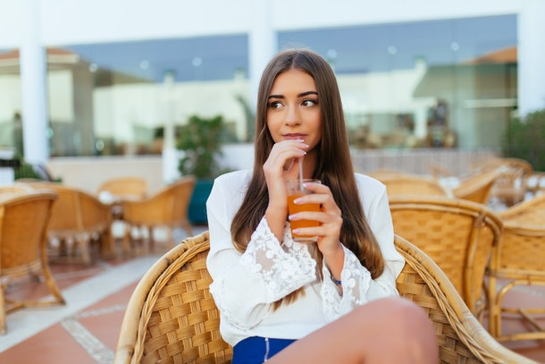 Beautiful young woman sitting in bar cafe, drinking fruit cocktail on a tropical beach