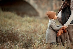 pretty little girl in brown hat and coat standing in the meadow in the park and kiss stomach of her pregnant mother at autumn