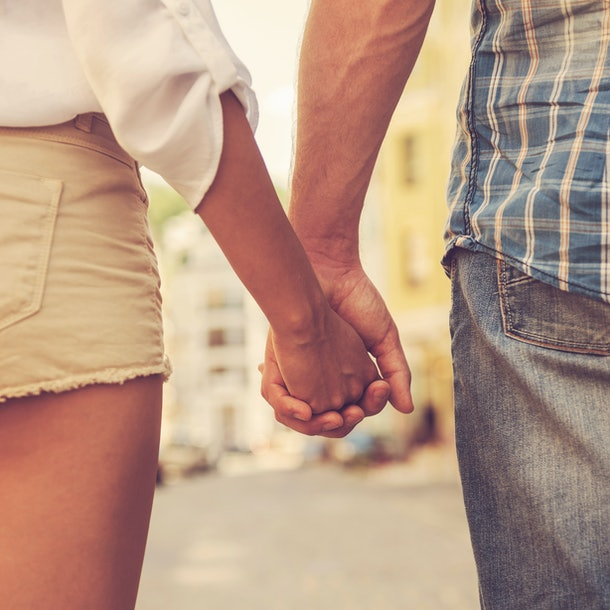 Hands and hearts together. Close-up of loving couple holding hands while walking outdoors
