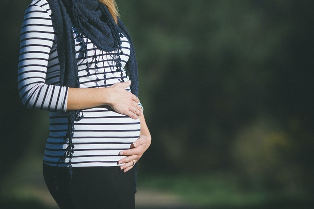 Pregnant woman in stripes with scarf holding belly on a blurred background