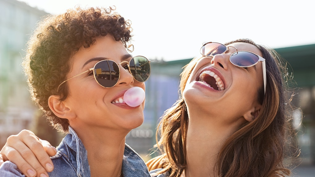 Young latin woman laughing while friend inflating bubble gum. Closeup face of multiethnic friends enjoying outdoor street. Brazilian girl laughing and blowing chewing gum with friend embracing her.