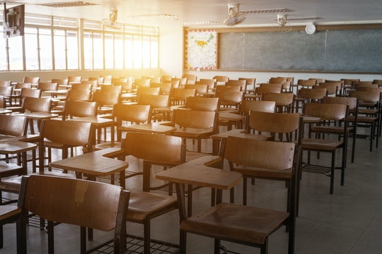 Empty school classroom with many wooden chairs. Wooden chairs in classroom. Wooden arranged in class...