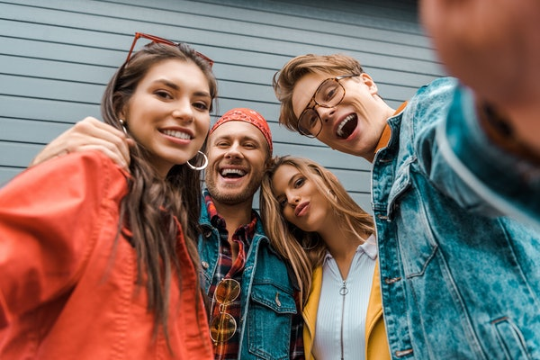 cheerful stylish friends taking selfie together