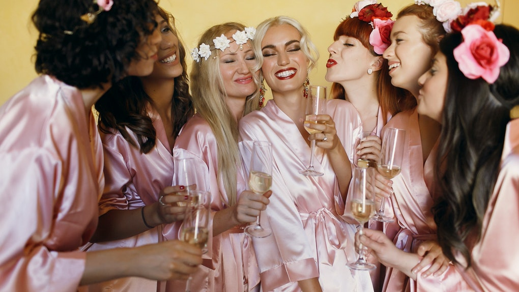 Pretty bridesmaids surround stunning bride posing in silk pink robes