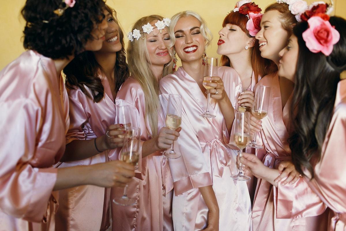 Pretty bridesmaids surround stunning bride posing in silk pink robes