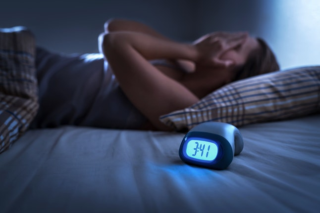 Sleepless woman suffering from insomnia, sleep apnea or stress. Tired and exhausted lady. Headache or migraine. Awake in the middle of the night. Frustrated person with problem. Alarm clock with time.
