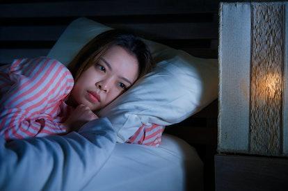 young beautiful sad and depressed Asian Korean girl lying on bed late night awake looking thoughtful...