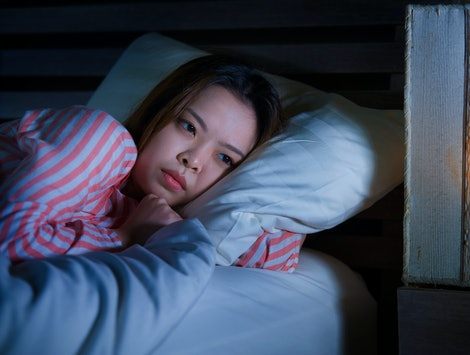 young beautiful sad and depressed Asian Korean girl lying on bed late night awake looking thoughtful suffering insomnia sleeping disorder feeling tired and worried in woman depression concept