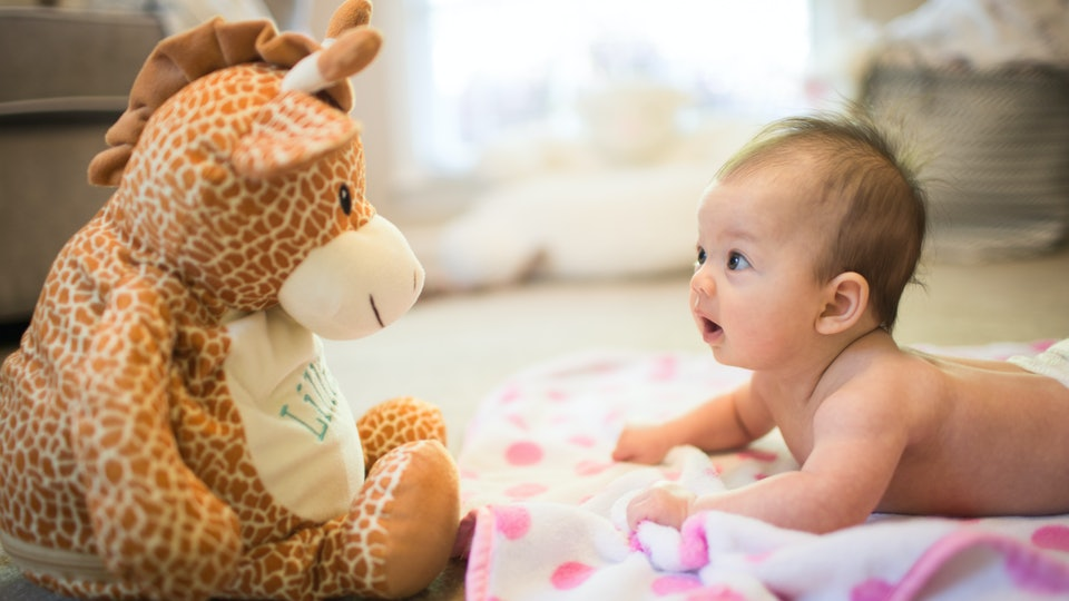 Baby Looking at Stuffed Animal Laying on Belly During Tummy Time