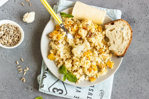Cauliflower rice with vegetables (onion and bell pepper). Organic paleo cauliflower rice on grey concrete  background. Copy space. Healthy concept.