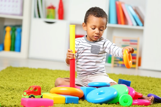 Little boy playing with his toys in the room