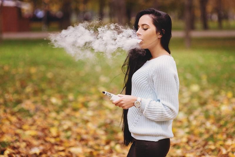 Woman vaping electronic hookah outdoor in autumn. Vape goodies