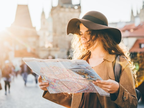 Girl with backpack looking at map, not being on her phone during vacation