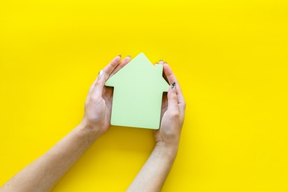Buy house with house figure in hands on office desk yellow background top view