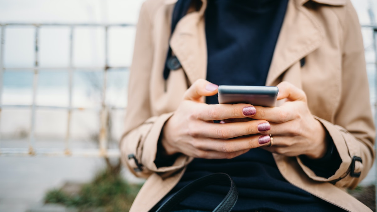 Young woman wearing beige coat using smart phone outdoors sitting near beach at spring. Cropped photo of female's hands holding mobile phone.