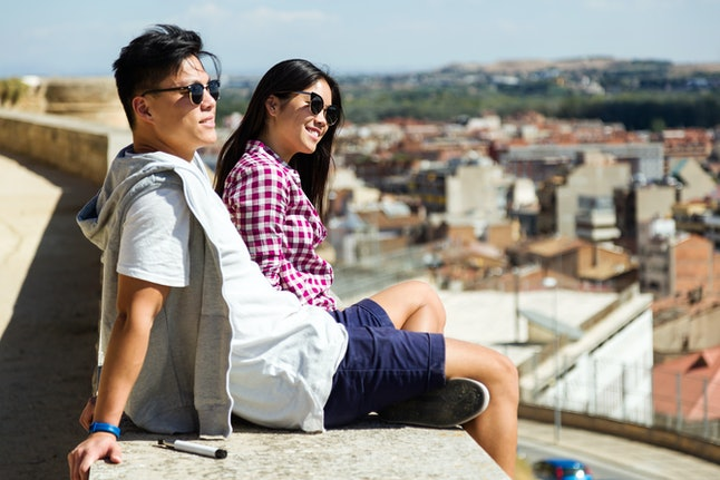Portrait of happy young couple looking at the views in the city.