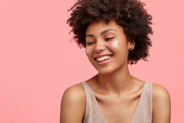 Studio shot of happy young African American female has glitter on cheeks, smiles happily with shy expression, has dark skin, stands against pink backgrounf with free space for your promotion