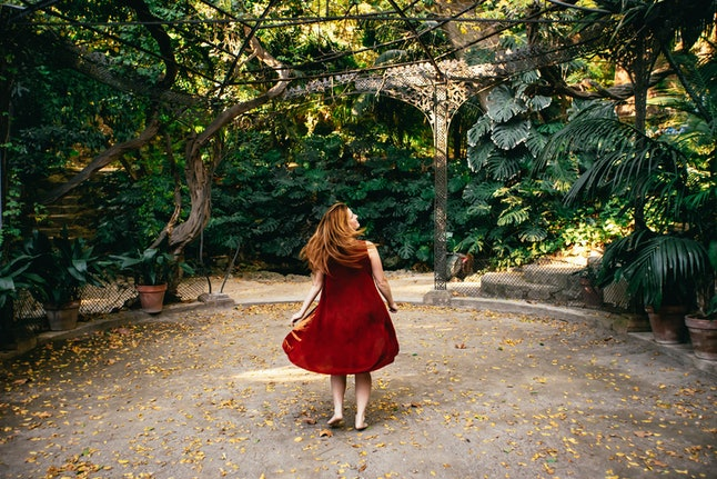 Happy woman twirling around in a red dress with her long hair flowing behind her on a footpath